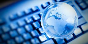 Un globe terrestre translucide flotte au-dessus d'un clavier d'ordinateur.
