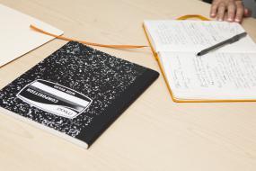 un carnet et des papiers et crayons sur une table