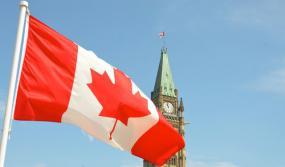 Photographie de la tour du parlement avec le drapeau canadien flottant en avant-plan.