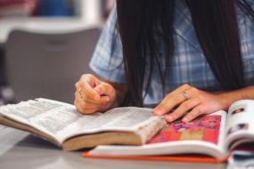 Photographie d'une personne avec deux livres ouverts devant elle.