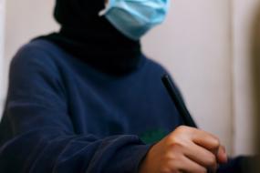 Photographie d'une personne portant un masque est tenant un crayon en position d'écriture.