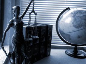 Sur un bureau, une statue de la justice, quatre livres et un globe terrestre.