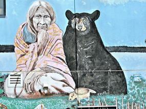 Art murale d'une femme autochtone assise à côté d'un ours noir.