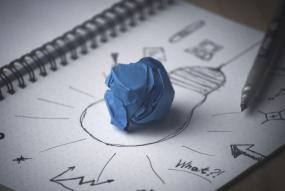 Photographie d'un cahier où on voit une ampoule avec des lignes qui partent dans tous les sens et un papier bleu chiffoné posé sur l'ampoule.