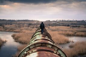 Une personne de dos se tient debout sur un pipeline.