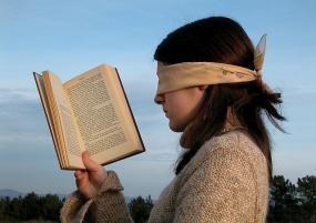 Une personne qui a les yeux bandées tient un livre devant ses yeux.