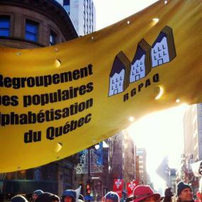 Une bannière à l'éfigie du Regroupement des groupes populaires en alphabétisation du Québec au dessus d'une foule de manifestant-e-s