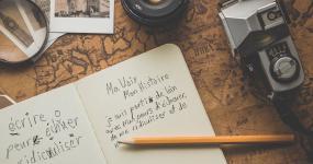 Vue sur un carnet sur une table, entouré d'une caméra, de photographies, d'une loupe et d'un crayon. Dans le cahier, un texte à l'écriture chambranlante.