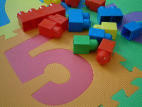 Un tapis-mousse coloré pour enfants avec des blocs éparpillés dessus.