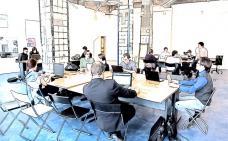 Photographie stylisée d'un espace de travail ou plusieurs personnes travaillent autour de grandes tables.