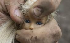 Une main sale tient la tête d'une poupée Barbie.