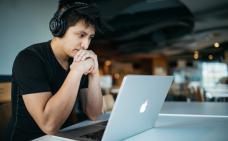 Photographie d'une personne qui regarde son écran d'ordinateur. Il porte un casque d'écoute et appui son menton sur ses mains liées.
