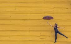 Sur un mur jaune, une personne semble s'envoler avec un parapluie.