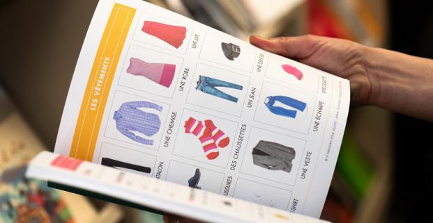 Photographie en gros plan de mains qui tiennent un livre ouvert, dont les pages du livre montrent une série d'illustrations de vêtements, avec leur nom en dessous. L'arrière-plan flou représente des étagères de bibliothèque.