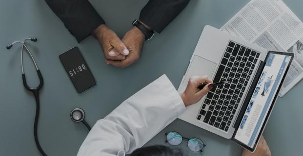 Plan de haut sur un bureau de médicin sur lequel on peut voir un stétoscope, un téléphone, des lunettes puis un ordinateur portable déposé sur un journal. D'un côté du bureau, les bras d'une docteur, avec un stylo à la main gauche, pointant vers l'écran de l'ordinateur. De l'autre côté, les bras d'un patient, mains ensemble.