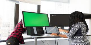 Photographie de deux personnes installant écrans et ordinateurs portables.