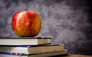 Photographie d'une pomme sur une pile de livres.