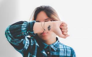 Photographie d'une personne qui cache le milieu de son visage avec son avant-bras.
