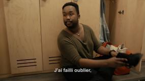 Capture d'écran de la vidéo. Un homme est assis sur un banc dans un vestiaire. En sous-titre, il est écrit « J'ai failli oublier. ».