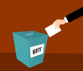 Illustration d'une main qui dépose un bulletin de vote.