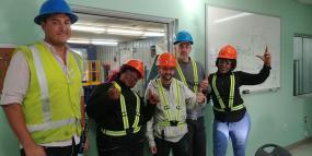 cinq personnes portant des casques et dossards de contruction sourient à la caméra