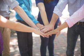 Six personnes posent une main les unes sur les autres.