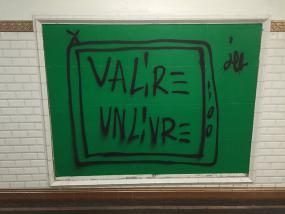 Un graffiti sur fond vert où l'on peut lire Va lire un livre.