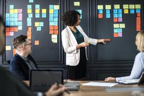 Une femme professionnelle debout présente, devant des collègues assis, un mur recouvert de post-it de différentes couleurs.