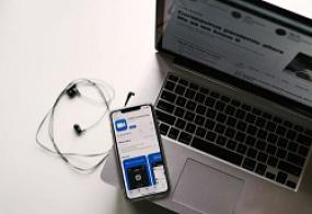Un téléphone portable affichant le logiciel Zoom est posé sur un ordinateur portable ouvert. Une paire d'écouteurs est posé à la gauche.