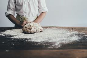 Photographie d'une boulangère ou un boulanger devant une planche où une pâte est déposée sur la surface enfarinée.