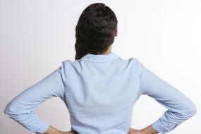 une femme de dos, les mains sur les hanches
