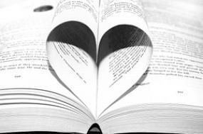 Photographie d'un livre ouvert dont deux pages repliées forment un coeur.