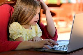 Photographie d'un enfant assis sur son parent qui travaille sur un ordinateur portable.