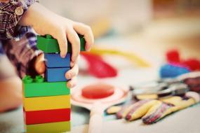 Photographie en gros plan sur les mains d'un enfant qui joure avec de gros blocs de couleur.