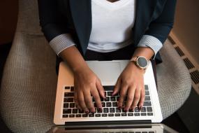 Vue en plongée sur les mains d'une personne qui travaille sur son ordinateur portable. Le plan est centrée sur les mains et le torse.