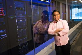 Une femme s'appuyant sur la vitre d'une salle de serveurs. Elle sourit à la caméra.
