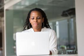 Photographie d'une femme racisée utilisant un ordinateur portable.