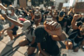 Photographie d'une manifestation, les personnes sont à genoux et le poing levé.