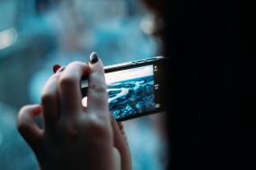 Vue de dos d'une personne qui regarge son téléphone portable.