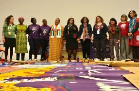 des femmes debout se tiennent la main devant une banderole posée sur le plancher