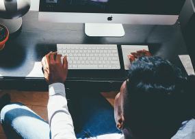 Photographie en plongée d'une personne travaillant à l'ordinateur.