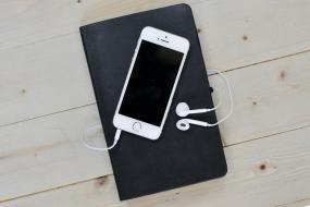 Un téléphone intelligent blanc avec ses écouteurs, sont placés sur un livre noir.