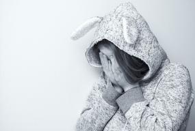 Photographie en noir et blanc d'une personne qui se cache le visage avec ses mains.