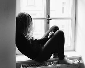 Photographie en noir et blanc d'une personne assise sur le rebord d'une fenêtre.