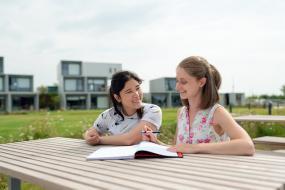 Une adulte et une enfant sont assises à l'extérieur à une table. Un cahier est déposé devant l'adulte qui tient un crayon.