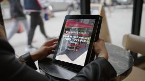 Gros plan sur une tablette électronique entre les mains d'une personne. L'information du cours en ligne est affiché à l'écran.