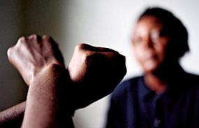 Deux bras croisées dont les poids sont fermés, avec une femme en arrière plan
