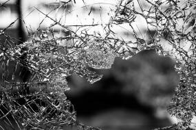 Photographie en noir et blanc d'une vitre brisée.