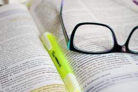 Photographie d'un livre ouvert : un surligneur jaune et des lunettes sont posés dessus.
