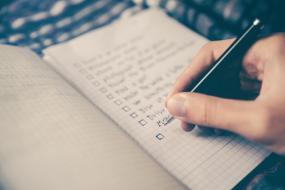 Gros plan sur le cahier où une personne y rédige une liste.